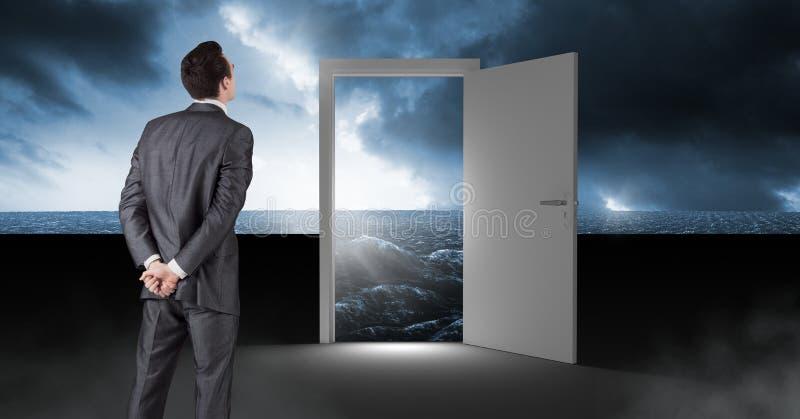 Zakenman die zich door open deur met surreal donkere overzeese gloed en hemel bevinden royalty-vrije stock afbeelding