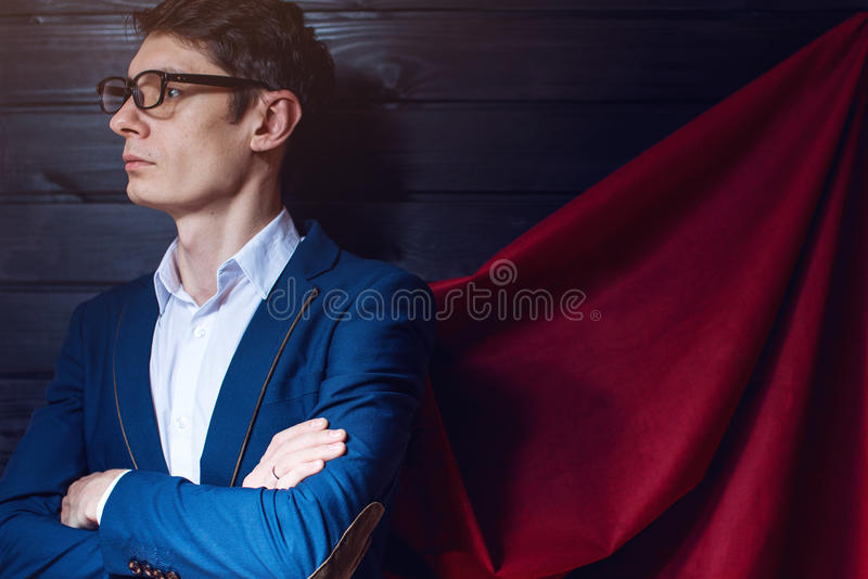 Zakenman die zich in een kostuum en een rode mantel zoals superhero bevinden stock foto's