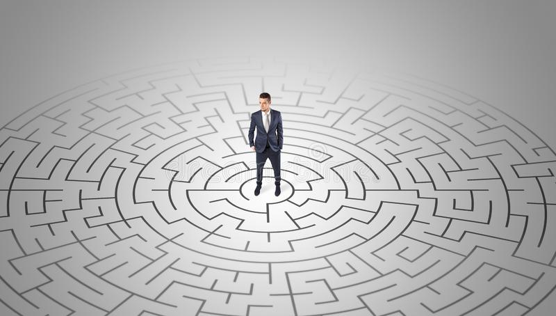 Zakenman die zich in een midden van een labyrint bevinden stock afbeeldingen