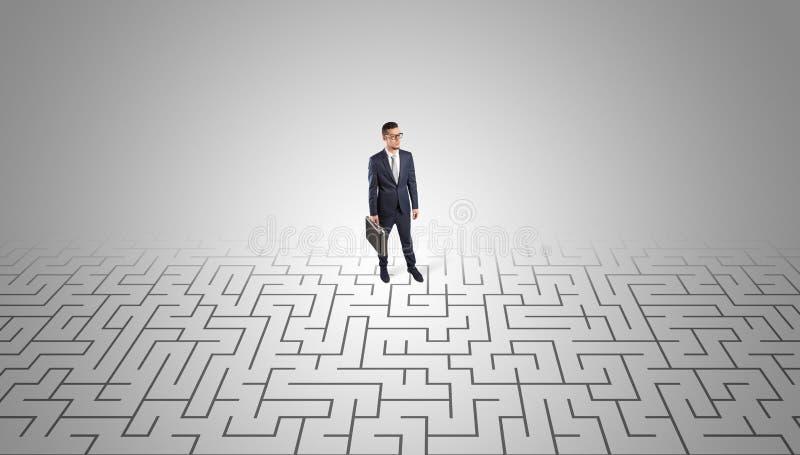 Zakenman die zich in een midden van een labyrint bevinden stock foto