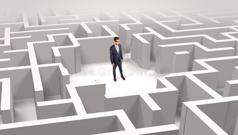 Zakenman die zich in een midden van een labyrint bevinden stock afbeelding