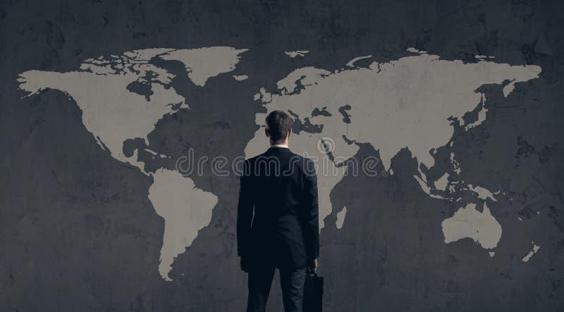 Zakenman die zich met aktentas bevinden De kaartachtergrond van de wereld Busi stock foto