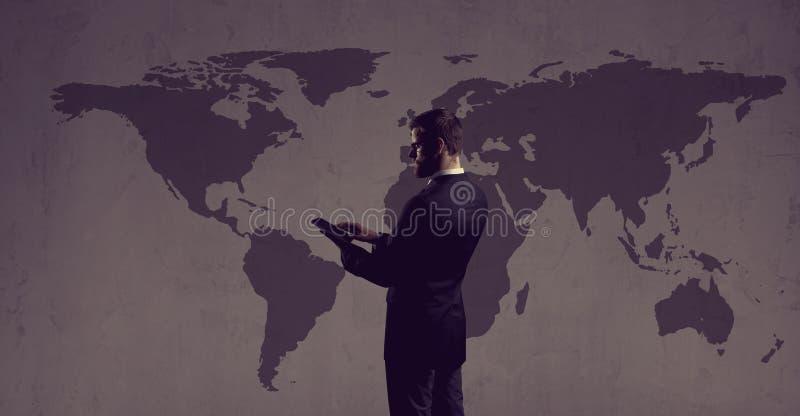 Zakenman die zich met computertablet bevinden De kaartachtergrond van de wereld stock afbeelding