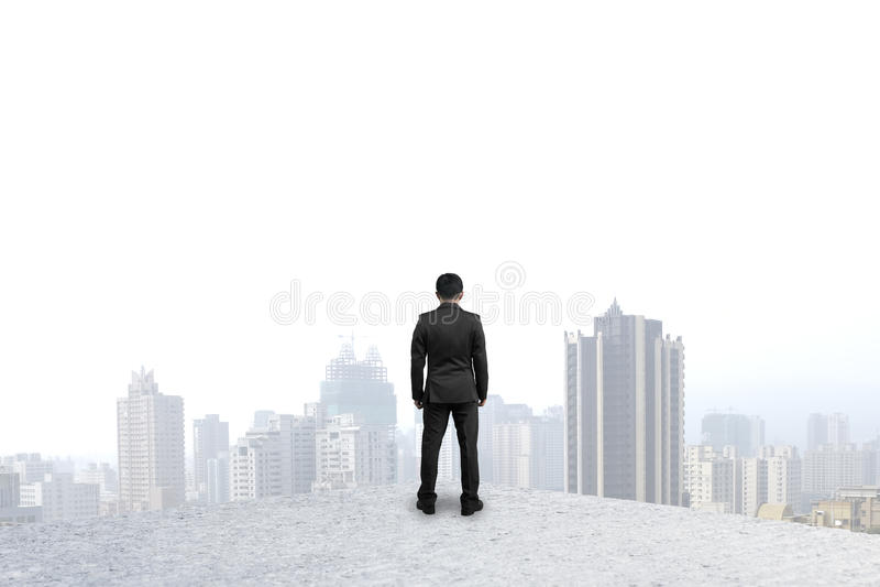 Zakenman die zich op concrete vloer bevinden die bij stad staren stock afbeelding