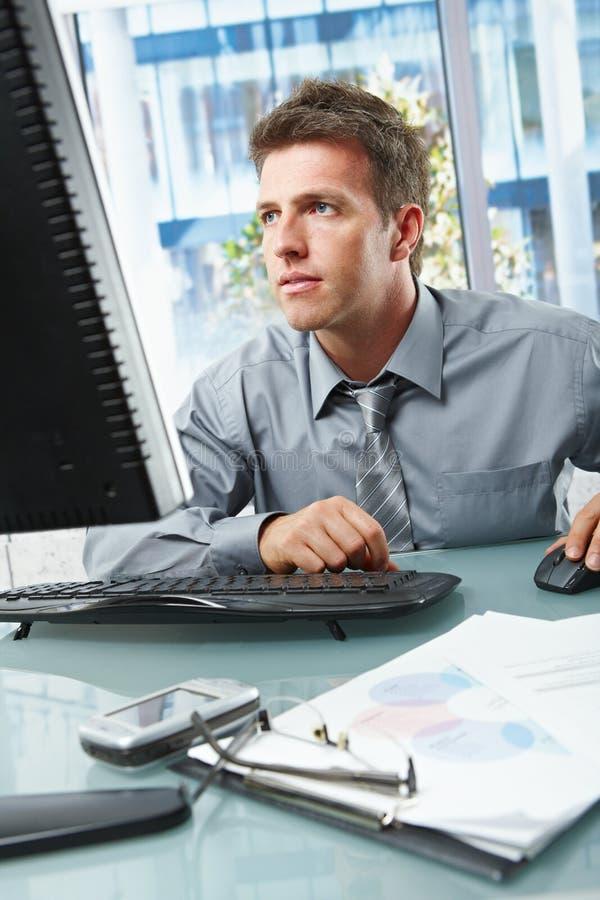 Zakenman die zich op het werk in bureau concentreren royalty-vrije stock foto