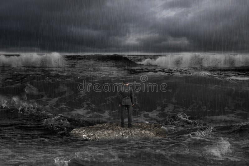 Zakenman die zich op rots bevinden die tegemoetkomende golven met donkere oce onder ogen zien stock fotografie