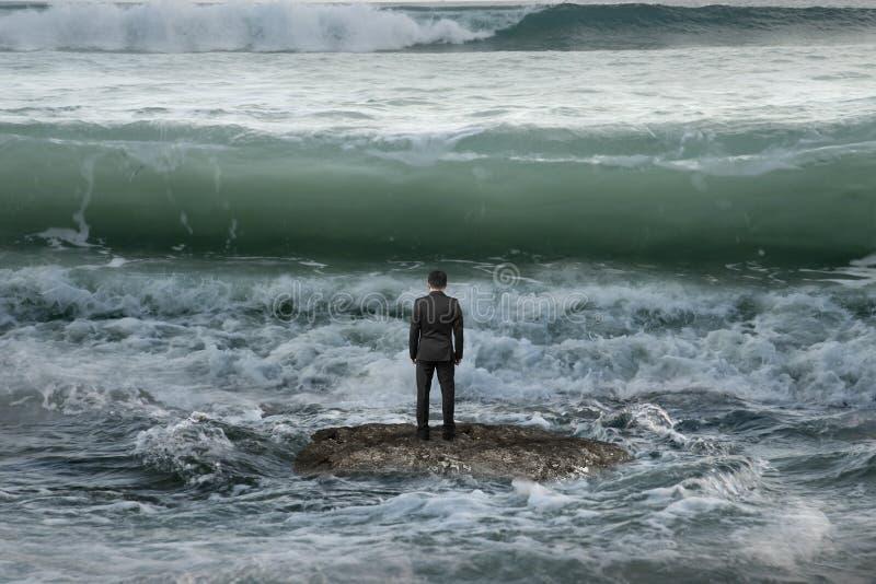 Zakenman die zich op rots in de oceaan bevinden die tegemoetkomende golven onder ogen zien royalty-vrije stock foto's
