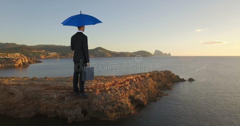 Zakenman die zich op rots met blauwe paraplu en aktentas bevinden terwijl op zee het kijken stock fotografie
