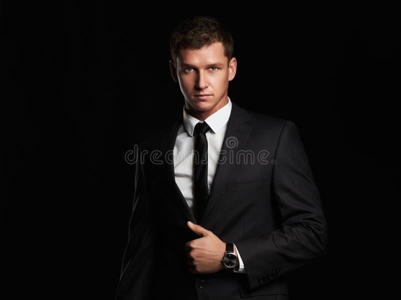 Zakenman die zich op zwarte achtergrond bevinden Knappe jonge mens in kostuum royalty-vrije stock fotografie