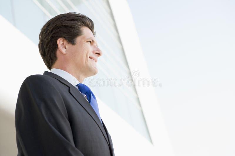 Zakenman die zich in openlucht door het glimlachen bevindt te bouwen royalty-vrije stock fotografie