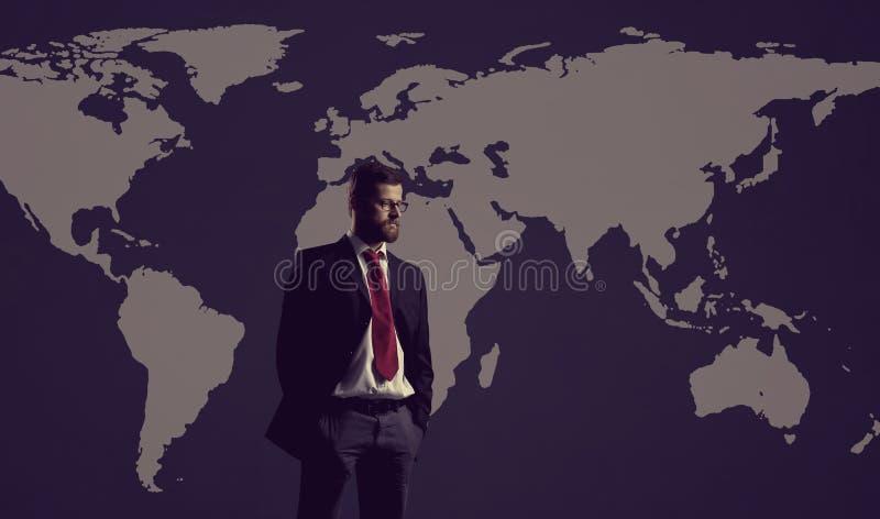 Zakenman die zich over de achtergrond van de wereldkaart bevinden Globale zaken, stock fotografie
