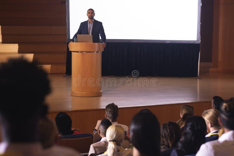 Zakenman die zich rond het podium bevinden en toespraak voor publiek in het auditorium geven stock afbeeldingen