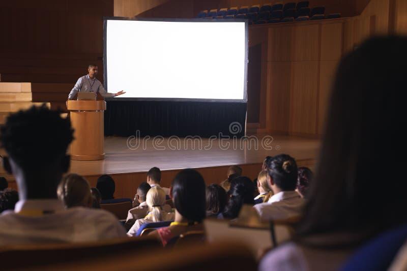 Zakenman die zich rond podium bevinden en presentatie in het auditorium geven stock fotografie