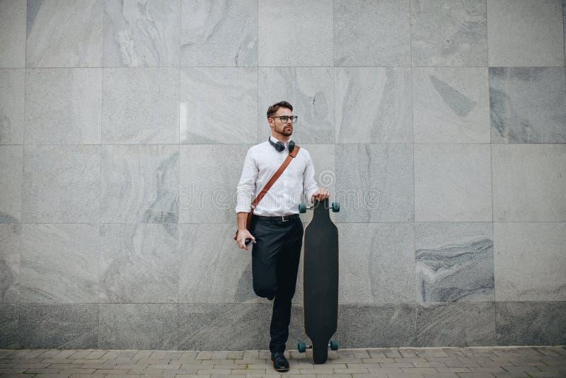 Zakenman die zich in straat bevinden die een longboard houden stock fotografie