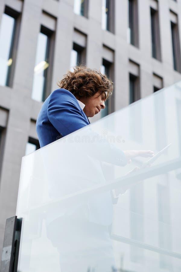 Zakenman die zich tegen de bureaubouw bevinden die een digitale tablet gebruiken stock fotografie