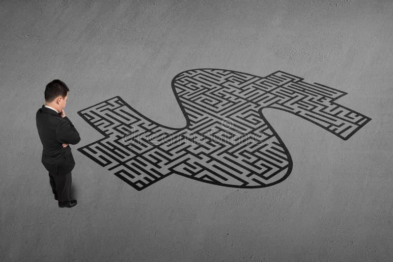 Zakenman die zich voor het labyrint van de geldvorm bevinden stock fotografie