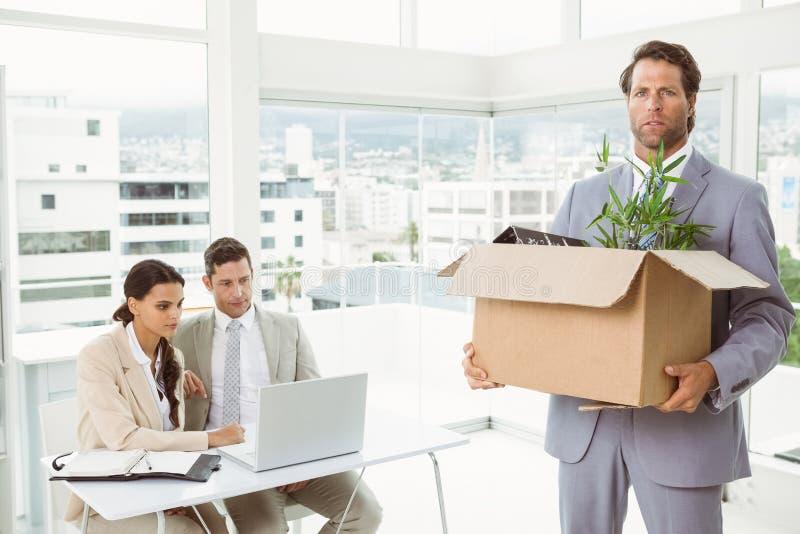 Zakenman die zijn bezittingen in doos dragen stock foto