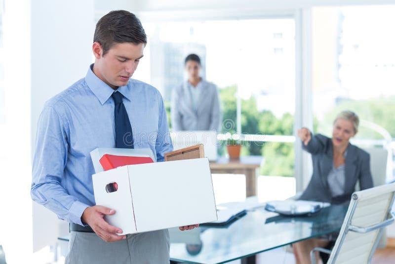 Zakenman die zijn bezittingen in doos dragen stock afbeeldingen