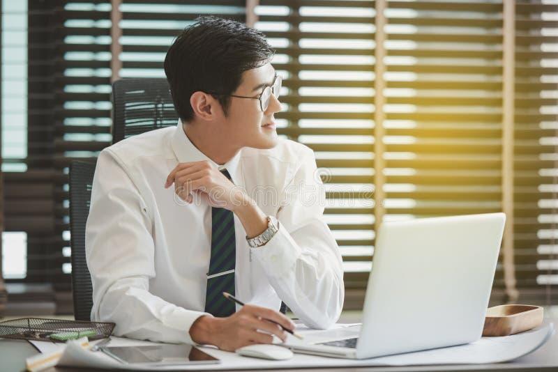 Zakenman die zijn computer in zijn bureau met behulp van royalty-vrije stock foto