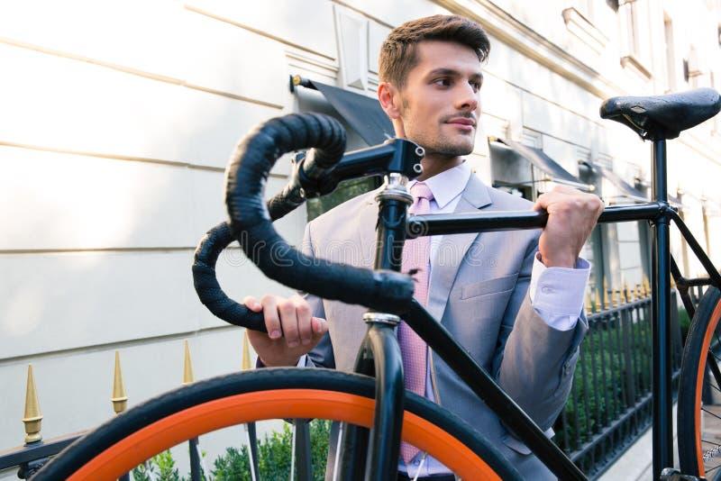 Zakenman die zijn fiets dragen stock afbeeldingen
