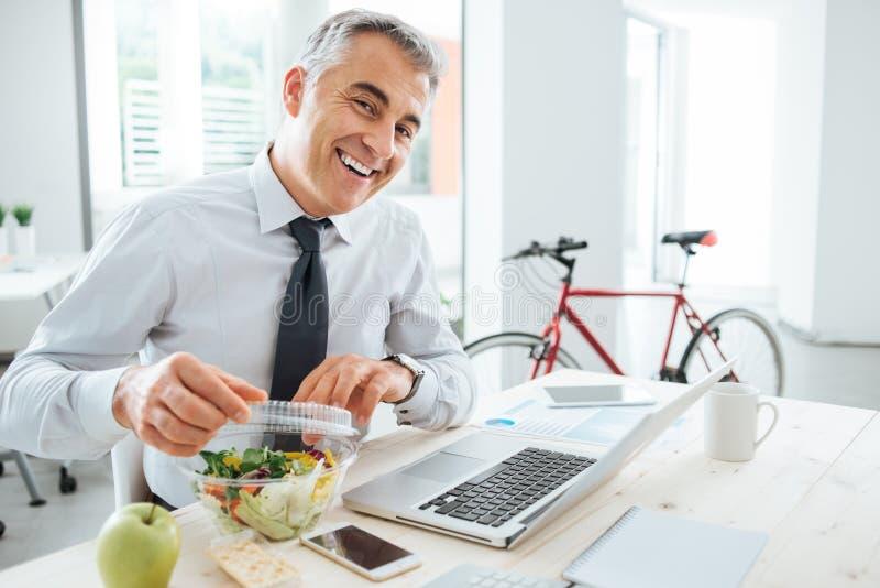 Zakenman die zijn saladepak openen royalty-vrije stock afbeeldingen