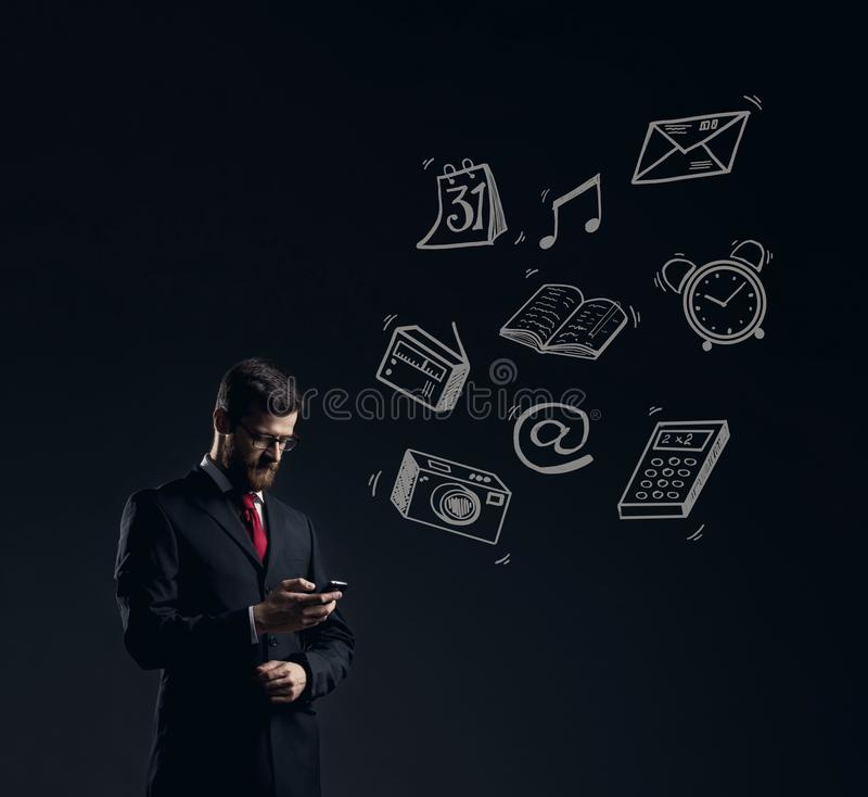 Zakenman die zijn smartphone over donkere dramatische backgroun controleren royalty-vrije stock afbeelding