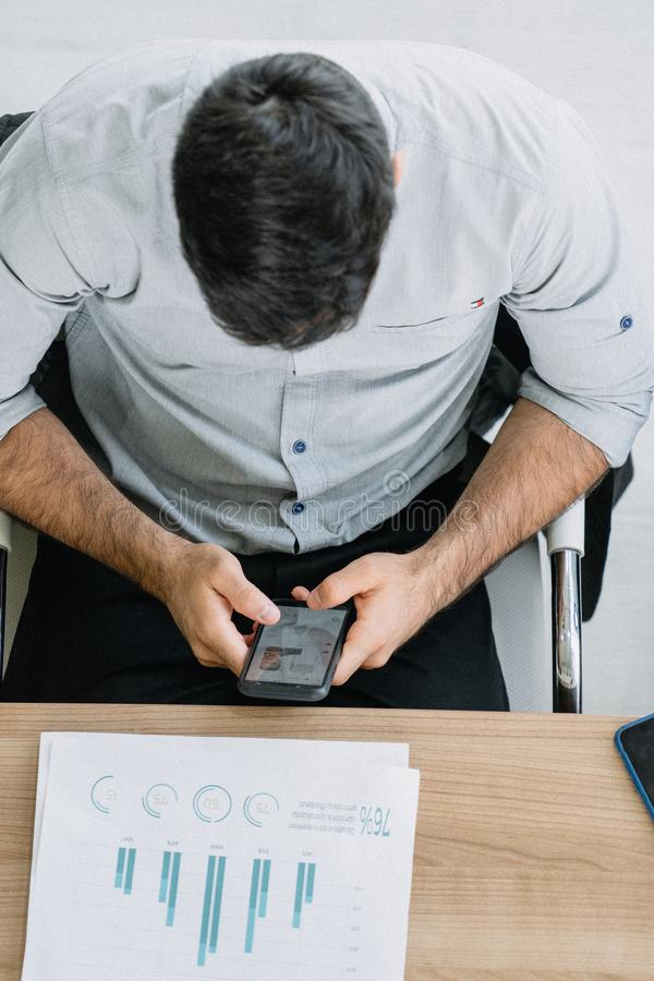 Zakenman die zijn smartphone witte vergadering speelt royalty-vrije stock fotografie