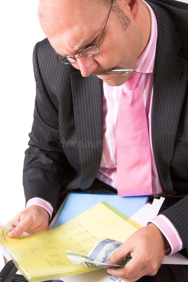 Zakenman die zijn spreadsheet controleert royalty-vrije stock afbeeldingen