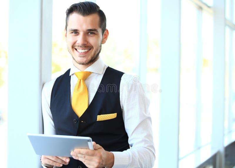 Zakenman die zijn tablet in bureau gebruiken royalty-vrije stock afbeelding