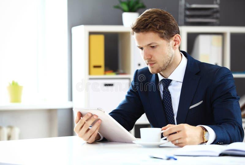 Zakenman die zijn tablet gebruiken stock afbeelding