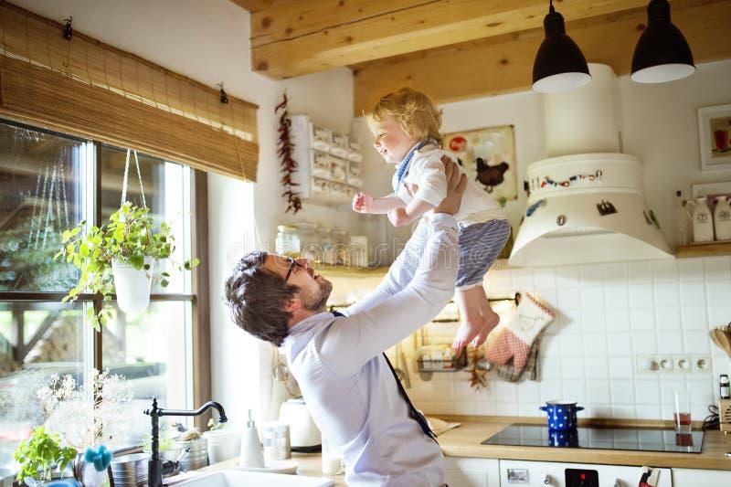 Zakenman die, zijn zoon houden in de lucht hoog naar huis komen die stock foto's