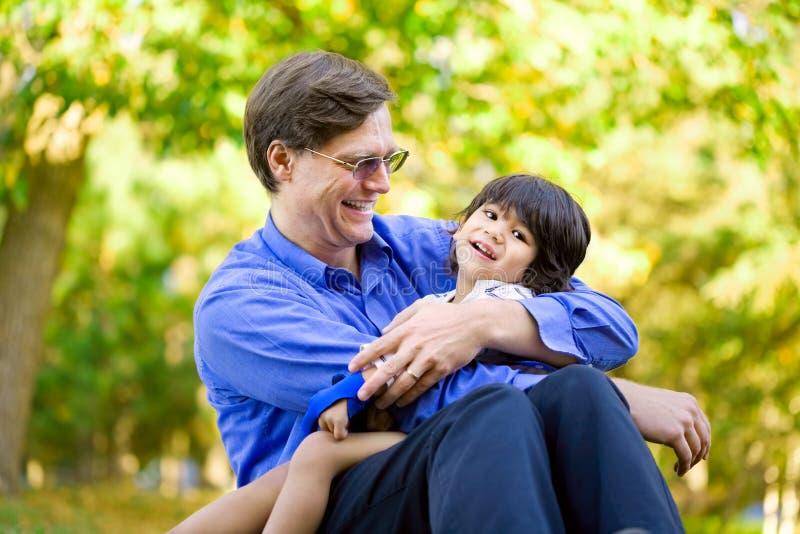 Zakenman die zijn zoon op gras houden stock foto's