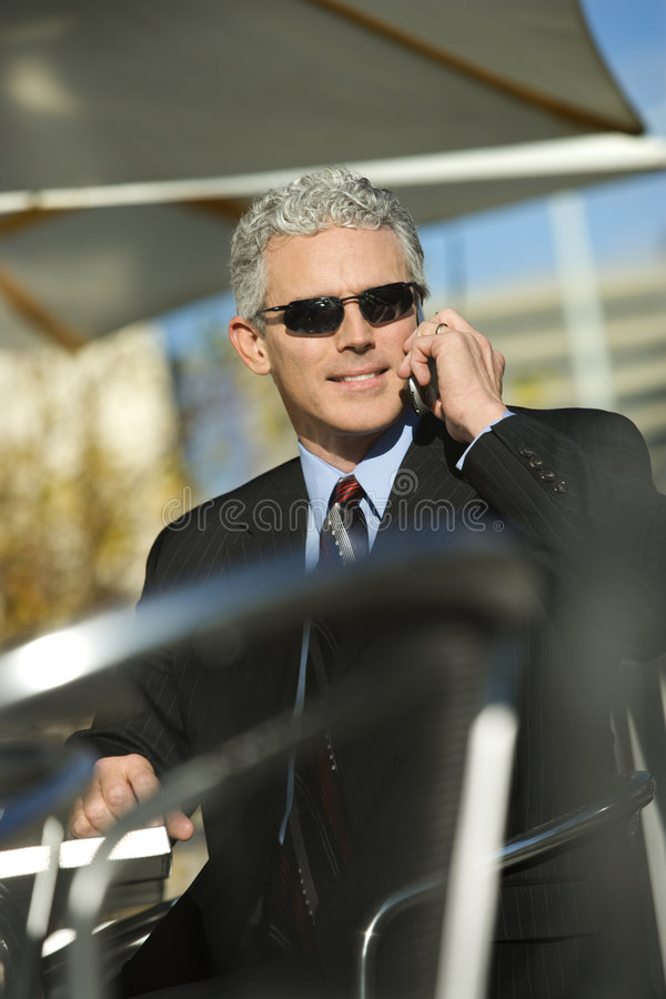 Zakenman die zonnebril draagt en op cellphone spreekt. royalty-vrije stock foto's