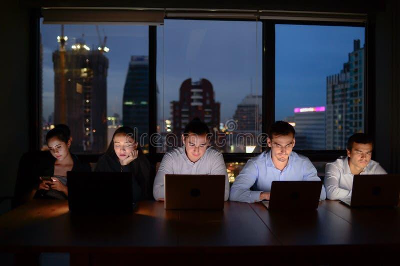 Zakenman drie en onderneemster twee die met computeroverwerk bij nacht werken stock foto