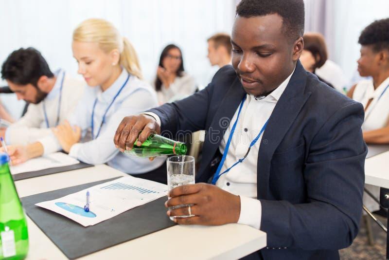 Zakenman drinkwater op handelsconferentie stock foto's