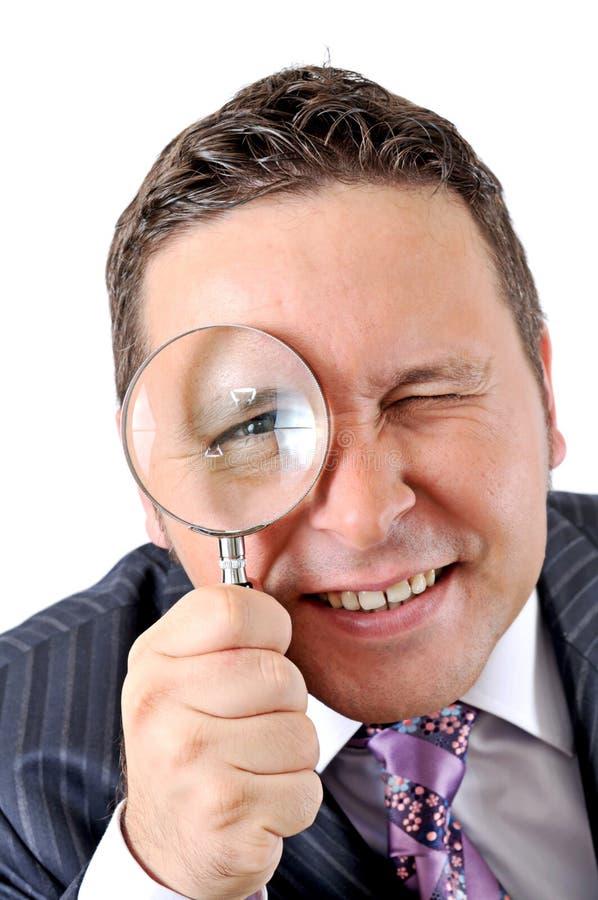Zakenman in een kostuum dat door een vergrootglas kijkt royalty-vrije stock afbeelding