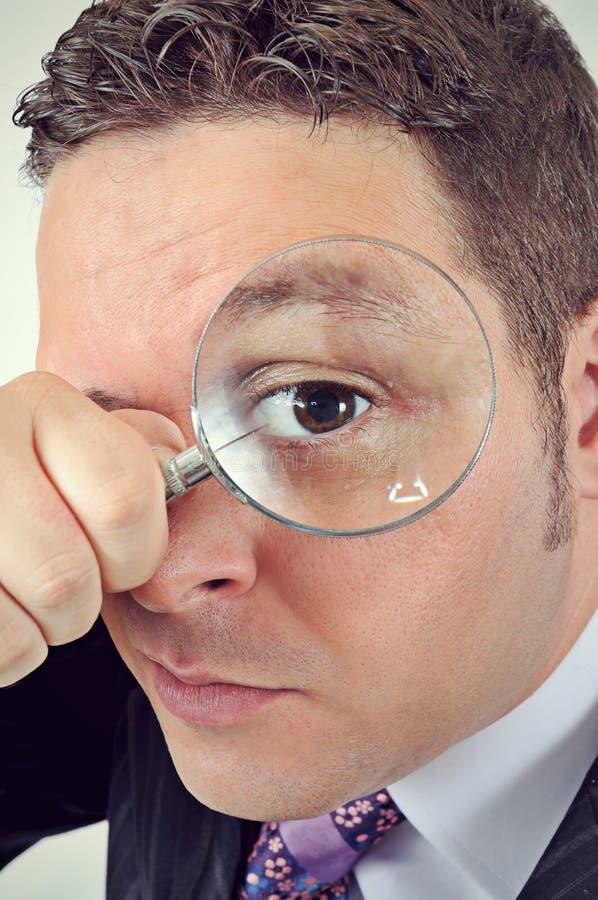 Zakenman in een kostuum dat door een vergrootglas kijkt stock foto's