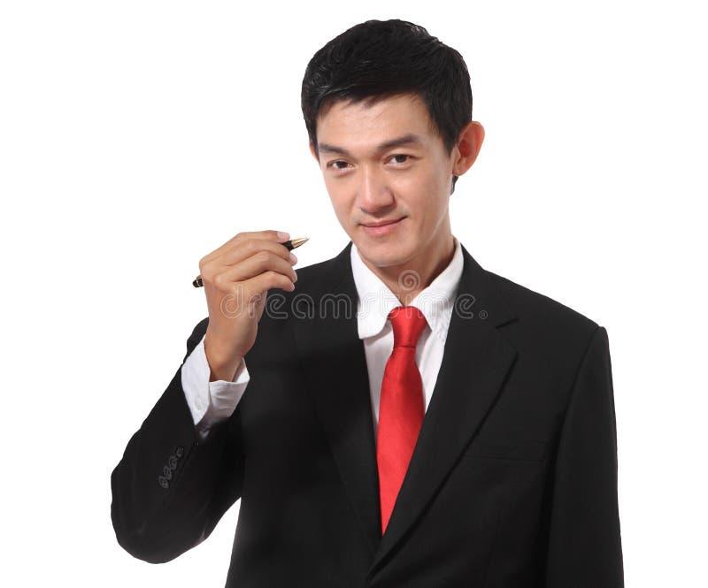 Zakenman in een kostuum met een gouden bandkleur die een pen houden en wr stock foto