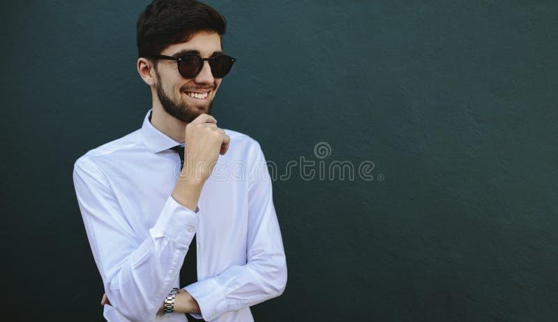 Zakenman in een zonnebril die wegkijkt en glimlacht royalty-vrije stock afbeeldingen