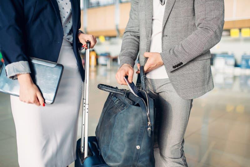 Zakenman en bedrijfsdame die in luchthaven wachten royalty-vrije stock fotografie