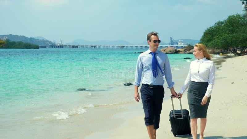 Zakenman en bedrijfsvrouw met een koffer die langs het witte zandstrand lopen op het eiland royalty-vrije stock fotografie
