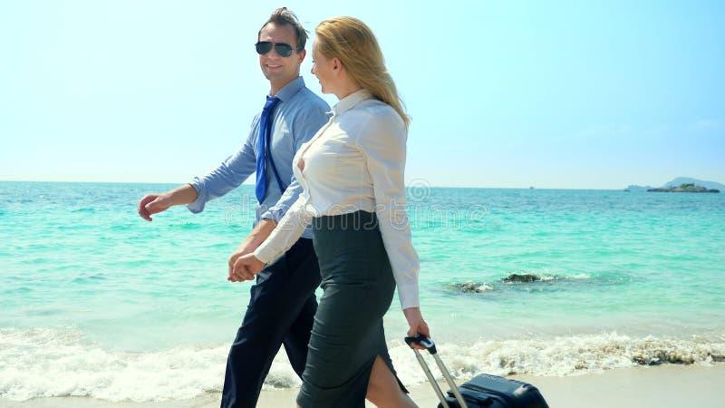 Zakenman en bedrijfsvrouw met een koffer die langs het witte zandstrand lopen op het eiland royalty-vrije stock foto's