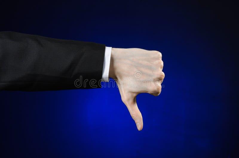 Zakenman en gebaaronderwerp: een mens in een zwart kostuum en een wit overhemd die handgebaar op een geïsoleerde donkerblauwe ach royalty-vrije stock afbeeldingen