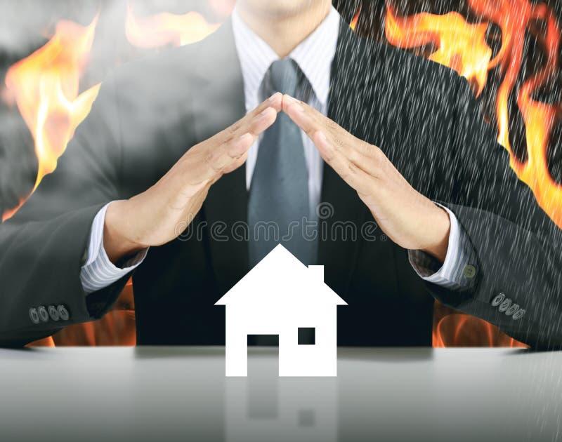 Zakenman en huis met brandachtergrond stock afbeeldingen