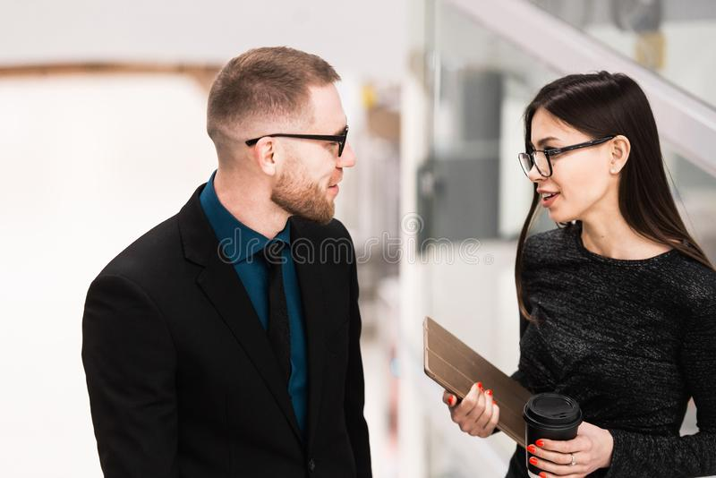 Zakenman en onderneemster die iets bespreken tijdens de koffiepauze stock afbeelding