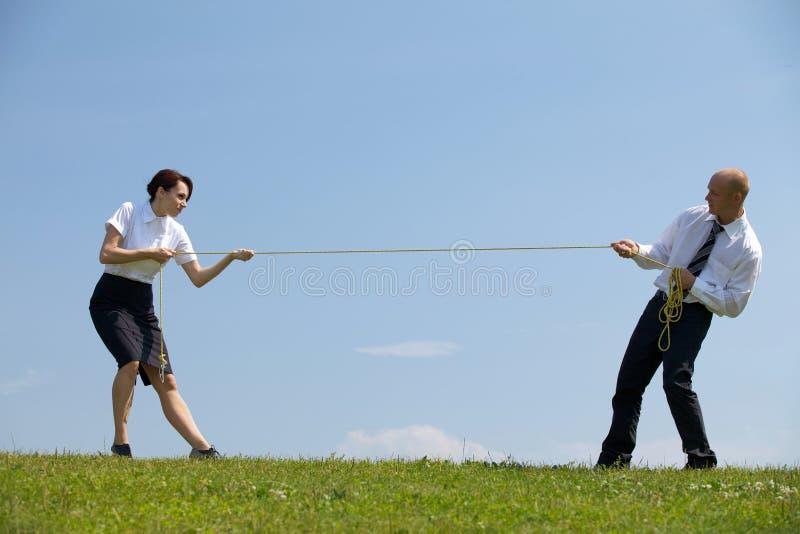 Zakenman en onderneemster in een touwtrekwedstrijd stock foto