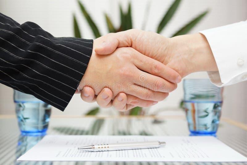 Zakenman en onderneemster het schudden overhandigt ondertekend contract royalty-vrije stock foto