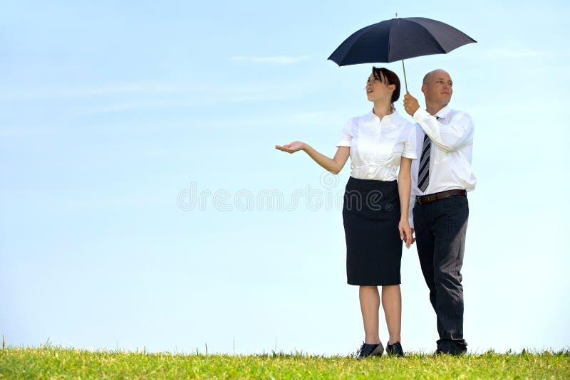 Zakenman en onderneemster onder paraplu in park royalty-vrije stock afbeelding