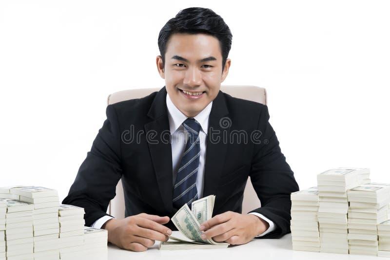 Zakenman en twee grote stapels van geld op bureau stock fotografie