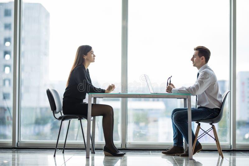 Zakenman en vrouw die een bespreking in het bureau hebben face to face bij lijst tegen vensters stock afbeelding